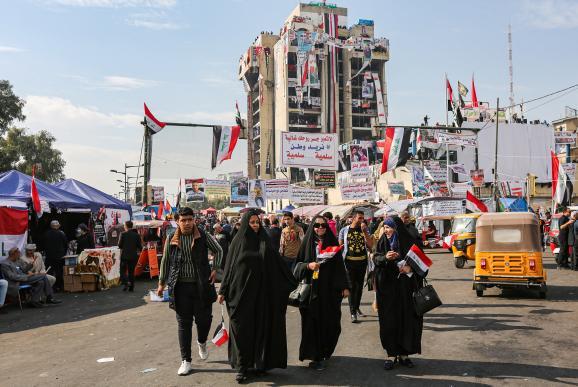 """Des femmes tiennent des drapeaux irakiens, sur la place Tahrir, devant le bâtiment occupé par les manifestants, \""""le restaurant turc\"""", le 23 novembre 2019, à Bagdad (Irak)."""