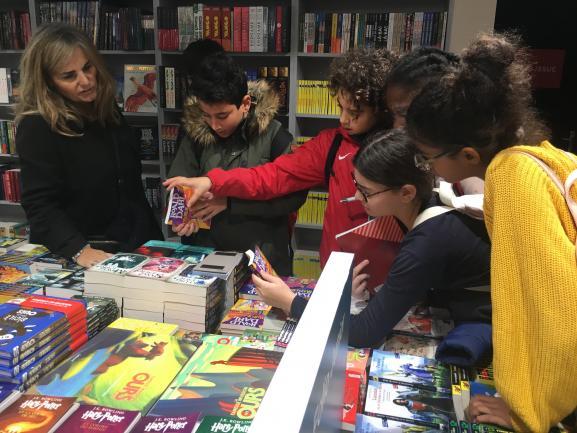Un groupe d\'enfants au Salon du livre et de la presse jeunesse de Montreuil, autour d\'une table présentant des classiques de la littérature, novembre 2019