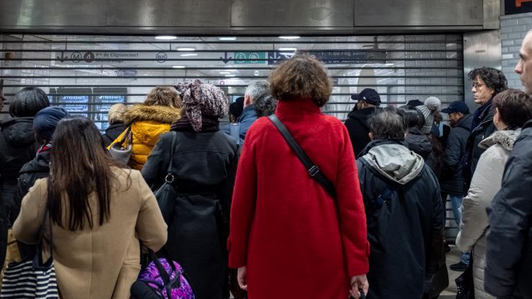 Des usagers du réseau RATP attendent devant l\'entrée du métro 4, en pleine grève contre la réforme des retraites, à Paris le 9 décembre 2019.