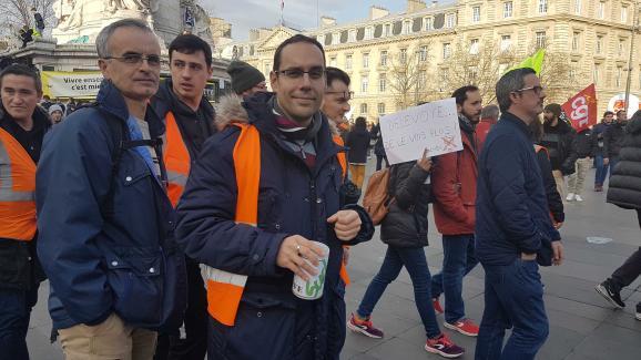 Cheminot à Niort, Lucien agite une cagnotte pour payer le bus du retour, mardi 17 décembre 2019, place de la République à Paris.