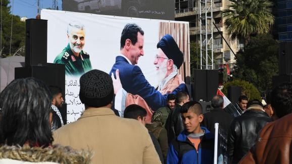 Des manifestants pro-régime à Alep (Syrie), le 7 janvier 2020, devant une affiche montrant le portrait de Qassem Soleimani et Bachar Al-Assad embrassant l\'ayatollah Ali Khamenei.