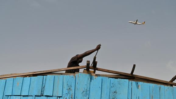 Un habitant démonte le toit de sa maison, contraint de quitter la zone de l\'aéroport.