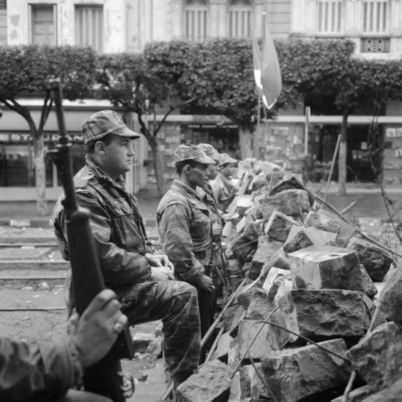 """Des parachutistes, qui ont fraternisé avec les insurgés, sont alignésle 31 janvier 1960 devant les barricades dresséesà Alger pendant la \""""emaine des barricades\""""."""