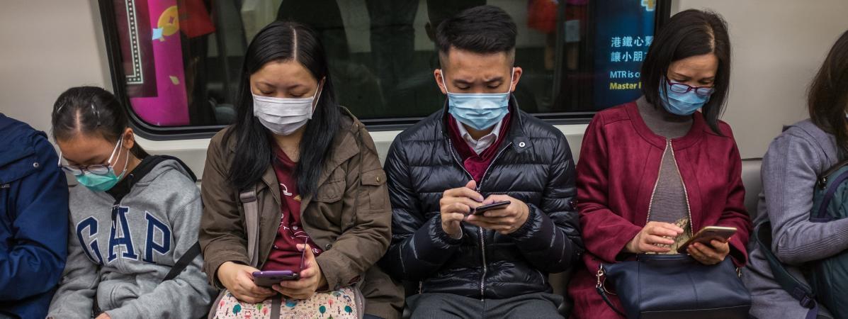Des personnes portent des masques dans un train à Hong Kong, le 25 janvier 2020.