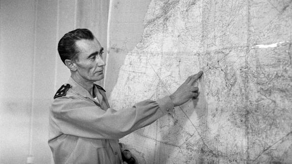 Le général JeanThiry indique aux journalistes français où se déroulera le premier essai nucléaire. Il montre sur la carte de l\'Algérie la région de Reggane dans le Sahara algérien. Photo prise en Algérie le 27 décembre 1960.