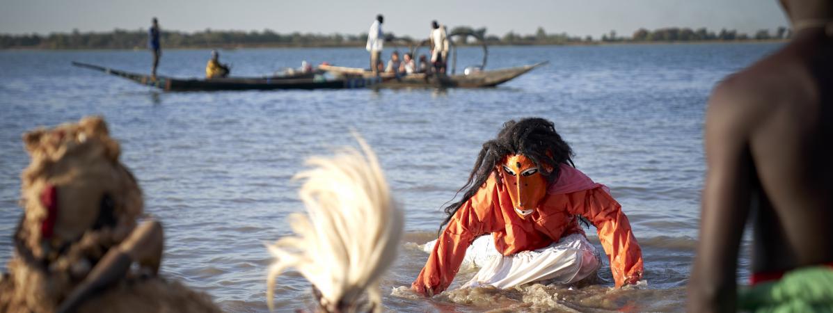 """Sortie des masques lors du \""""Ségou Art Festival\"""" sur les rives du fleuve Niger au Mali. Selon la légende, les Bozo sont les descendants de Faaro, esprit de l'eau et créateur du monde, ici représentation du mythe de la sirène. Photo prise le 7 février 2020 à Ségou."""