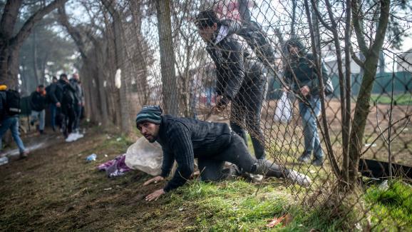 Un migrant traverse une barrière lors d\'affrontements avec la police grecque à Pazarkule, dans le district d\'Edirne, le 29 février 2020.