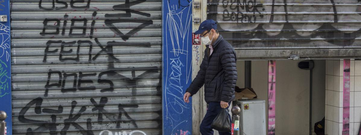 Un hommepasse devant des magasins fermés à cause de l\'épidémie de coronavirus, à Paris, le 15 mars 2020.