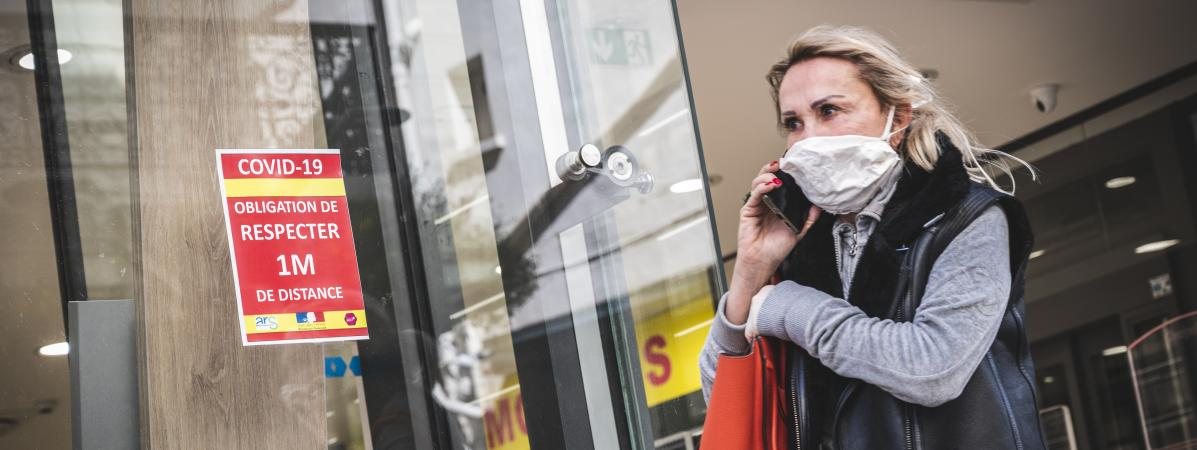 Une femme quitte une pharmacie pendant l\'épidémie de Covid-2019, le 16 mars 2020, à Cannes (Alpes-Maritimes),