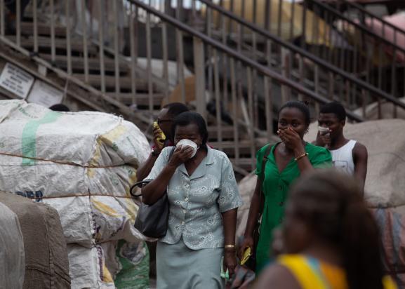 Des passants se protègent pendant une opération de désinfection contre le coronavirus sur un marché d\'Accra (Ghana) le 23 mars 2020.