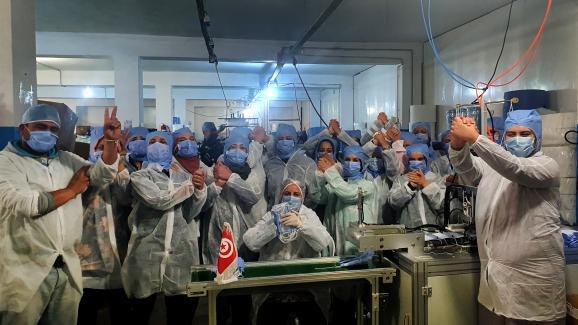 Les employé(e)s fier(e)s de continuerà fabriquer des masques dans leur usine à Kairouan, le 26 mars 2020.