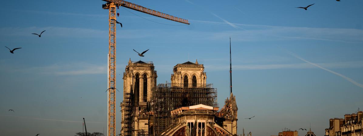 Notre-Dame de Paris, surmontée d\'une grue à l\'arrêt et toujours enserrée dans son échaffaudage, un an après l\'incendie du 15 avril 2019.