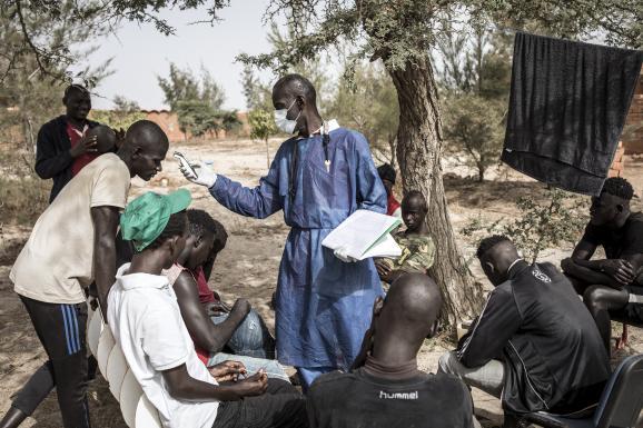 Un agent sanitaire prend la température de jeunes sans-abri, confinés en quarantaine, près de Dakar le 10 avril 2020.