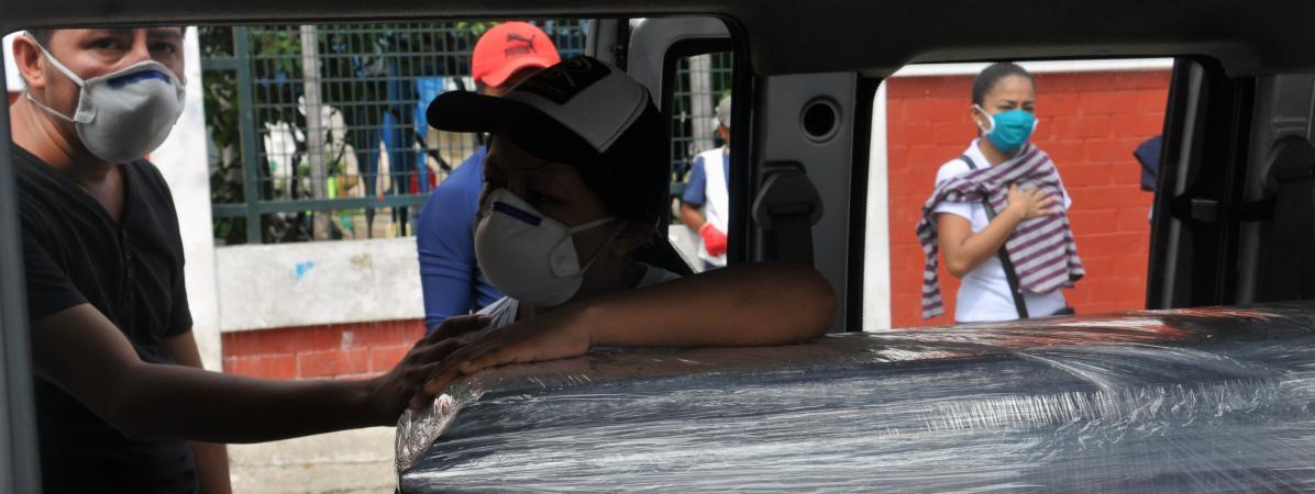 Des proches d\'une personne emportée par le Covid-19 se tiennent près de son cercueil pour ses obsèques, le 23 avril 2020 àGuayaquil (Equateur).