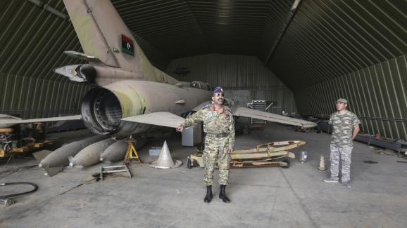 La base aérienne Al-Watiya renfermait armes et munitions selon le porte-parole du GNA. On y voit aussi de vieux avions de chasse en partie démontés.