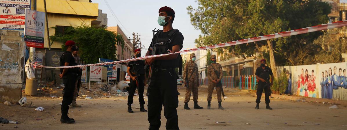 Des forces de sécurité pakistanaises sécurisent la zone de Karachi où un avion s\'est écrasé, samedi 23 mai 2020.