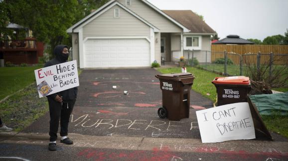 Un manifestant devant une maison présentée comme celle du policier Derek Chauvin, le 27 mai 2020 à Oakdale, dans le Minnesota.