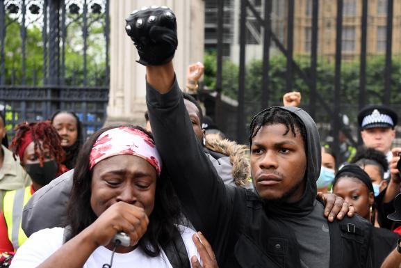 """John Boyega, poing levé parmi d\'autres manifestants de la marche de protestation sur le thème \""""Black Lives Matter\"""", le 3 juin 2020 à Londres, après la mort de l\'Afro-Américain George Floyd, tuélors de son interpellation à Minneapolis quelques jours plus tôt"""