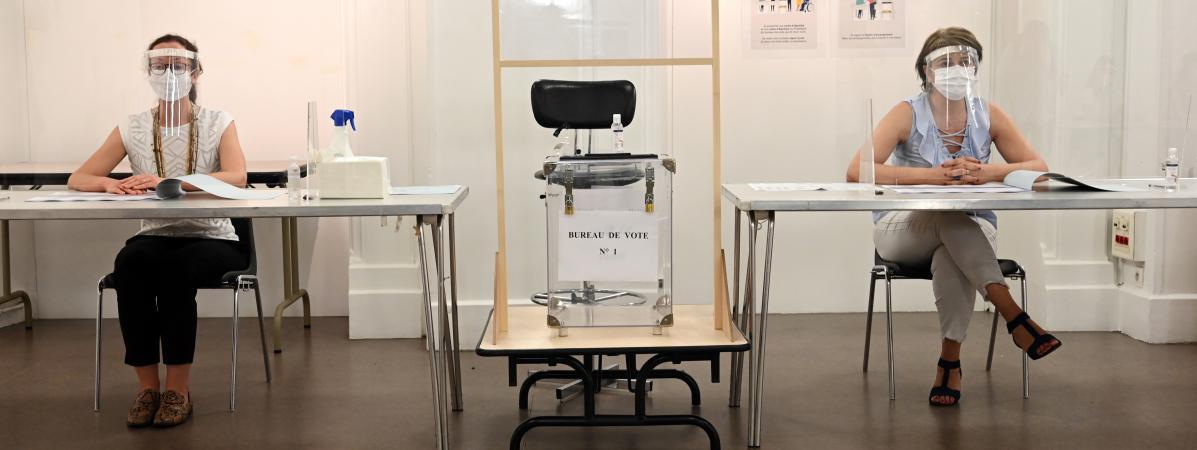 Masques, visières, parois en plexiglas : un dispositif sanitaire complet était mis en place dans ce bureau de vote parisien, le 28 juin 2020, pour le second tour d\'élections municipales perturbées par la crise sanitaire.