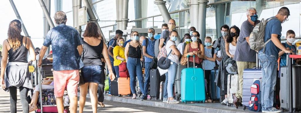 Des voyageurs patientent à l\'extérieur de l\'aéroport Felix-Eboue à Cayenne, en Guyane, le 10 juillet 2020.