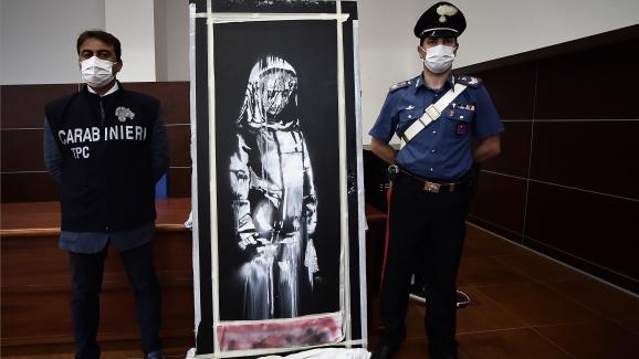 """Δύο Ιταλοί αστυνομικοί πλαισιώνουν το """"Το λυπημένο κορίτσι"""", ένα έργο τέχνης του δρόμου που αποδίδεται στον Banksy.  11 Ιουνίου 2020"""