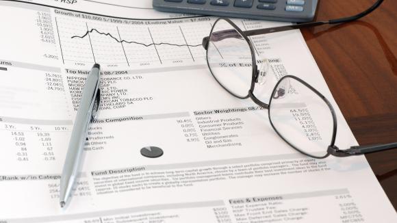 Stylo, lunettes, calculatrice et article financier. Photo d'illustration.