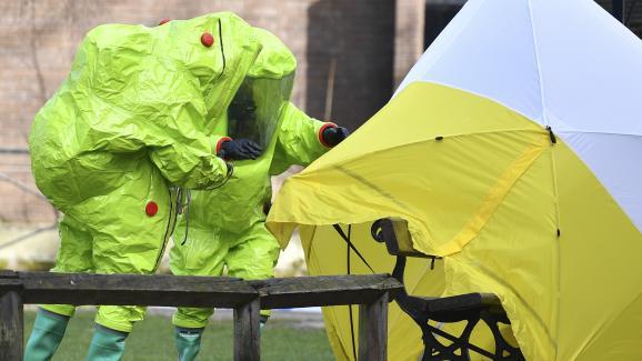 Deux membres des services d\'urgence fixent une tente autour du banc où ont été retrouvés Sergueï Skripal et sa fille, le 8 mars 2018 à Salisbury (Angleterre).