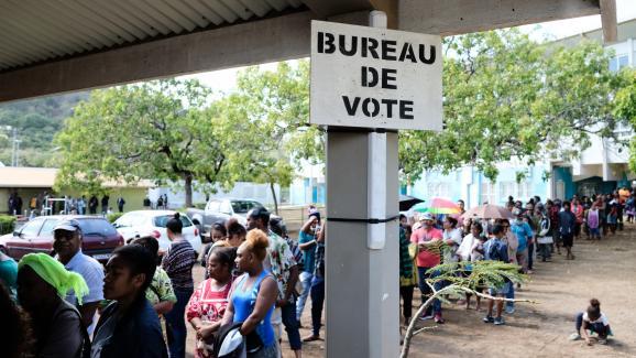 Des personnes attendent devant un bureau de vote, le 4 octobre 2020, à Nouméa.