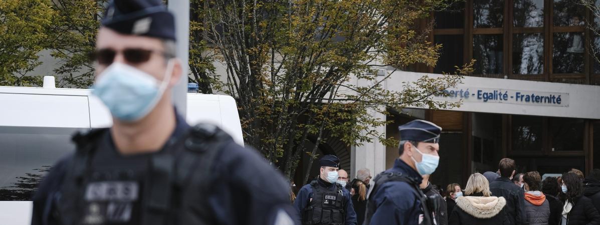 Des policiers en faction devant le collège du Bois d\'Aulne à Conflans-Sainte-Honorine où enseignait Samuel Paty.