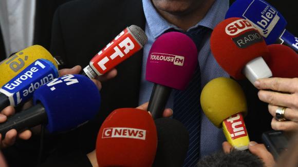 Des micros tenus par des journalistes en train d'interviewer un homme.