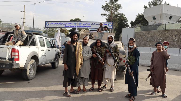 Des talibans se tiennent devant l\'aéroport de Kaboul en Afghanistan, jour du départ des derniers soldats américains du pays, le 31 août 2021.