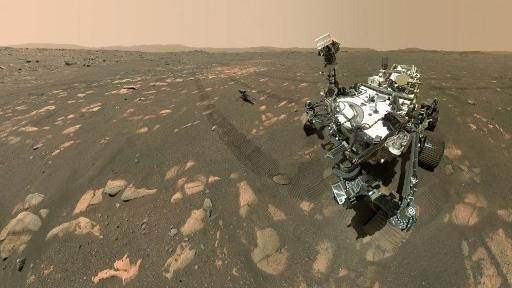 This NASA photo shows the Perseverance Mars rover in a selfie with the Ingenuity helicopter, seen here about 13 feet (3.9 meters) from the rover, on April 6, 2021, the 46th Martian day, or sol, of the mission and taken by the WATSON (Wide Angle Topographic Sensor for Operations and eNgineering) camera. - NASA is targeting no earlier than Sunday, April 11, for Ingenuity Mars Helicopter?s first attempt at powered, controlled flight on another planet. A livestream confirming Ingenuity?s first flight is targeted to begin around 3:30 a.m. EDT Monday, April 12. (Photo by Handout / various sources / AFP)