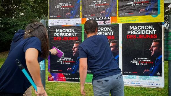 """Des adhérents du mouvements des """"Jeunes Avec Macron"""" collent des affiches de campagne devant la mairie de Lille."""