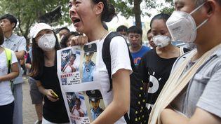 Des familles de victimes de la catastrophe de Tianjin (Chine)laissent éclater leur colère contre la gestion du drame par les autorités, le 16 août 2015. (AFP)