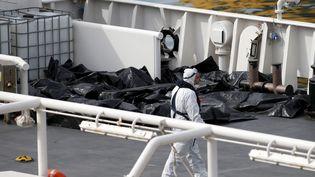 Les corps de migrants morts lors du naufrage de leur embarcation en Méditerranée sont disposés sur le pont d'un bateau des garde-côtes italiens, à L'Isla (Malte), le 20 avril 2015. (DARRIN ZAMMIT LUPI / REUTERS)