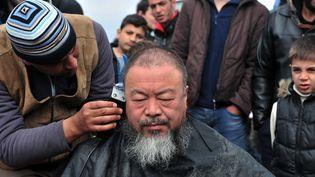 Séance de coiffure pour Ai Weiwei à Idomeni, en Grèce, auprès des migrants, le 17 mars 2016  (Sakis Mitrolidis / AFP)