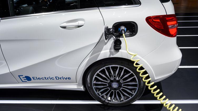 Une voiture électrique est en train de se recharger. (FABRICE COFFRINI / AFP)