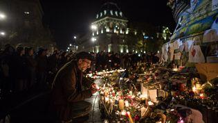 Un homme dépose une bougie sur un mémorial improvisé en mémoire des victimes des attentats, place de la République, à Paris, le 15 novembre 2015. (GEAI LAURENCE / SIPA)