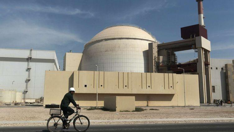 Un homme à vélo passe devant la centrale nucléaire de Bushehr, dans le sud de l'Iran, le 26 octobre 2010. (MAJID ASGARIPOUR/AP/SIPA)