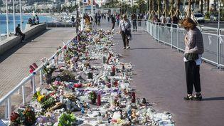 Le 10 octobre, une femme regarde les fleurs déposées sur la promenade des Anglais à Nice en hommage aux victimes de l'attentat du 14 juillet. (CITIZENSIDE/JEAN-LUC THIBAULT / AFP)
