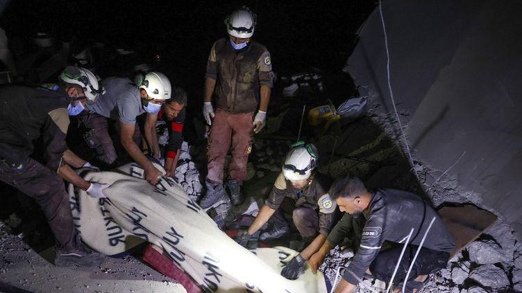 Des membres de la défense civile syrienne extirpent le corps d'une femme des décombres dans le village d'Ehsim (Syrie), le 18 juillet 2021. (OMAR HAJ KADOUR / AFP)