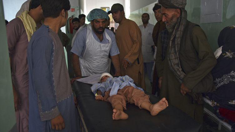 Un enfant blessé est transporté sur une civière vers un hôpital après un attentat à la voiture piégée à Kandahar le 6 juillet 2021 (JAVED TANVEER / AFP)