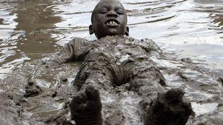 """Un jeune garçon s'amuse dans une mare de boue à l'occasion du Mud Day (""""Jour de la Boue"""") à Westland (Michigan, Etats-Unis), le 9 juillet 2013. (PAUL SANCYA / AP / SIPA)"""