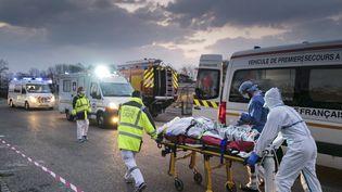 A Mulhouse, un patientatteint du Covid-19 est transporté d'un hôpital militaire à une ambulance, avant d'être transféré dans un TGV médicalisé, le 29 mars 2020. (SEBASTIEN BOZON / AFP)