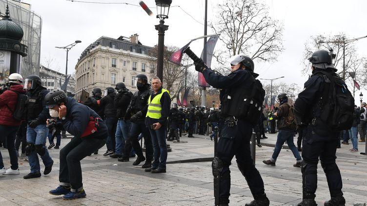 """Un membre des forces de l'ordretire une grenade lacrymogène à proximité d'un journaliste, lors de la manifestation des """"gilets jaunes"""" à Paris, le 8 décembre 2018. (ALAIN JOCARD / AFP)"""