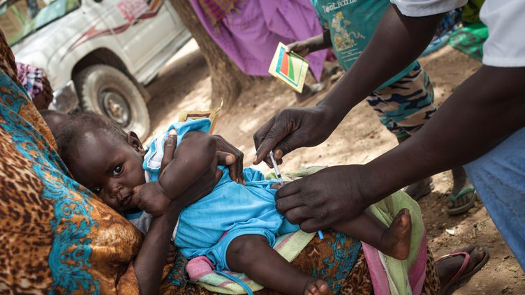 Un enfant se fait vacciner lors d'une campagne menée par les autorités sanitaires avec le soutien de l'ONG française Première Urgence Internationale (PUI), dans le village d'Agang, dans l'est du Tchad, le 25 mars 2019. (AMAURY HAUCHARD / AFP)