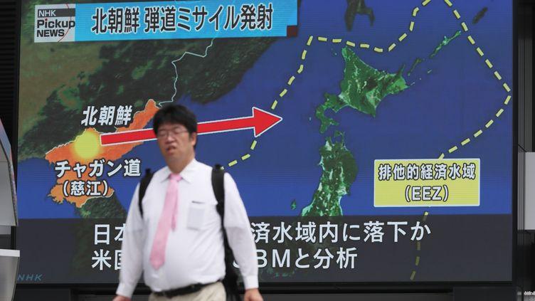 Un homme passe devant un écran modélisant le trajet d'un missile nord-coréen, le 29 juillet 2017 à Tokyo (Japon). (KUNIHIKO MIURA / YOMIURI)