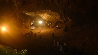 De jour comme de nuit, les sauveteurs tentent de localiser l'équipe de football. À l'entrée de la grotte, ils ont installé un véritable campement. (LILLIAN SUWANRUMPHA / AFP)