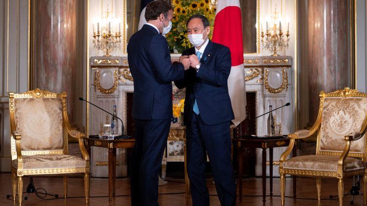 Le président français Emmanuel Macron et le Premier ministre Japonais, le 24 juillet 2021 à Tokyo (Japon). (CHARLY TRIBALLEAU / AFP)