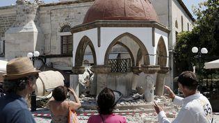 Des touristes regardent la mosquée Defterdar sur l'île de Kos (Grèce), le 12 juillet 2017. (COSTAS BALTAS / REUTERS)